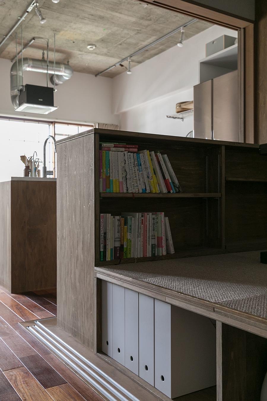 上げた床下は、一部収納にもなっている。キッチンとは低めの本棚でゆるやかに仕切られている。