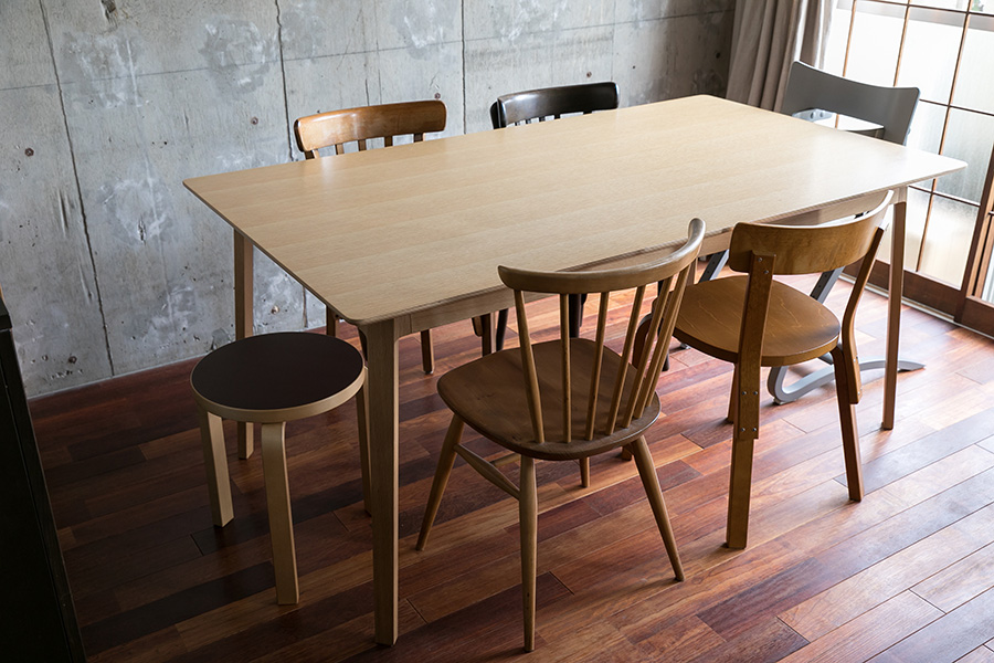 床材は赤褐色のケンパス材をDIYでオイル塗装した。ダイニングテーブルを囲むイスは、アンティークのものなど、あえてバラバラの個性を楽しんでいる。