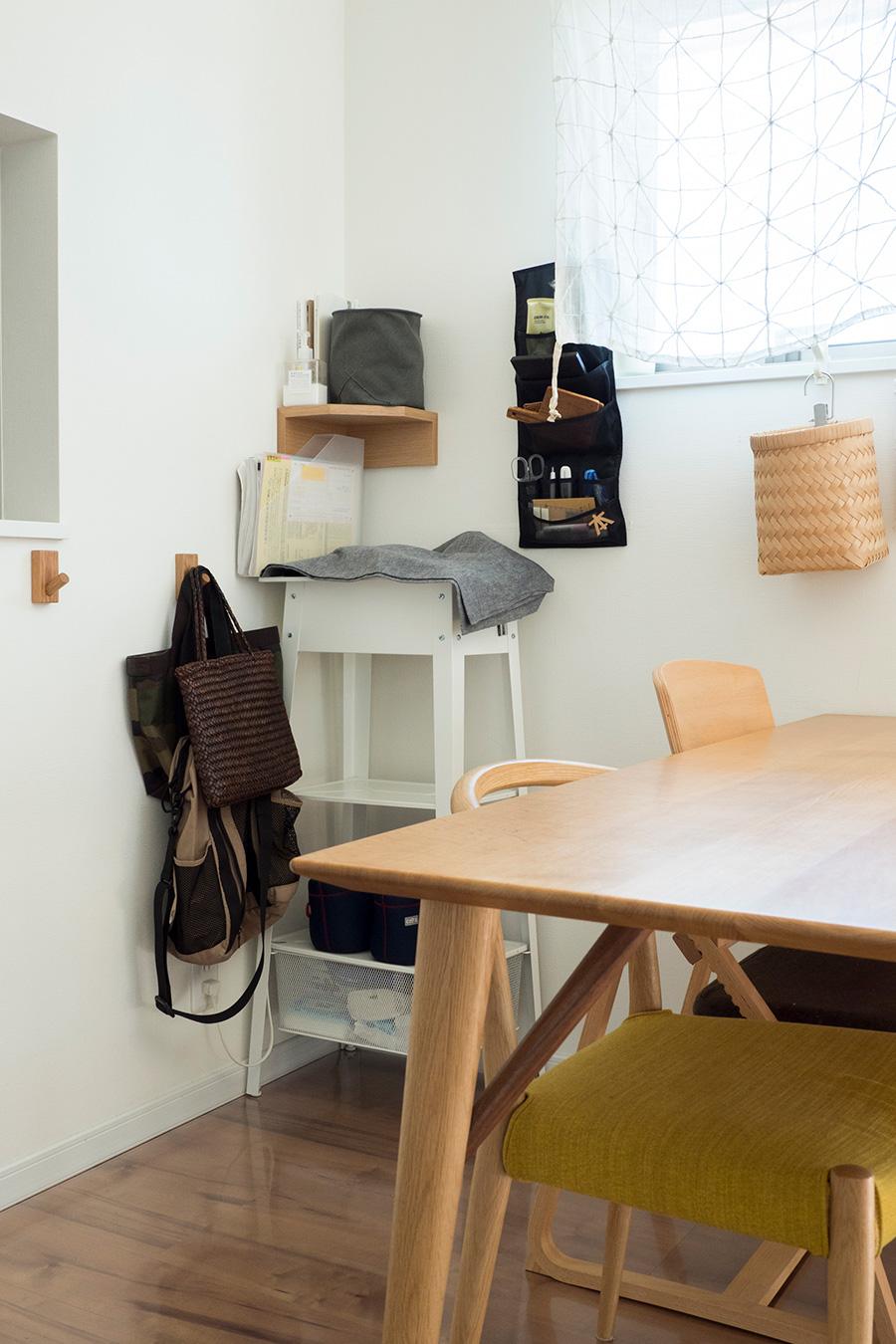 仕事の効率を考えたワークスペース&ダイニング。白いラップトップテーブルの上にPCをスタンバイ。その上に取り付けたコーナー家具はカバンの中身の特等席で、帰宅したらカバンの中から出した財布やポーチなどをここに出している。窓下のカゴはゴミ入れ。ダイニングのどこからも手が届き掃除の邪魔にもならないので、床置きのゴミ箱より便利。