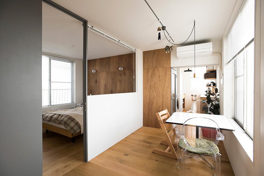 リビング側からキッチン方向を見る。南北にある開口から入る光が、内部開口を通り抜ける。天井の高さまであるドアは、グレーに塗装。
