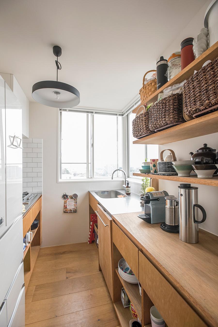 「木とステンレスで統一したかった」というキッチン。シンクやキッチン台の下は、使いやすいようにあえて扉をつけずざっくりと。
