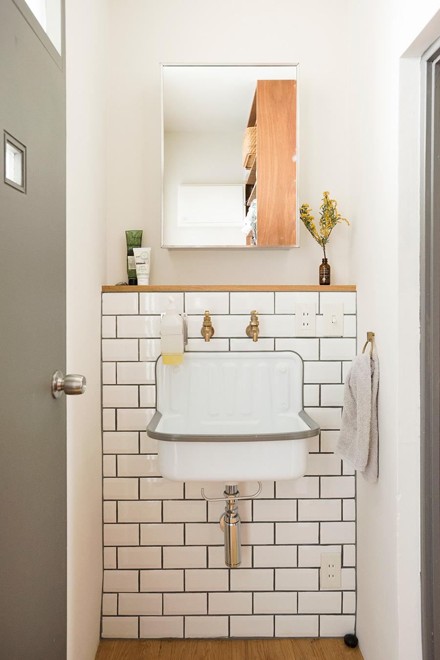 孝祐さんこだわりの洗面。立体的なサブウェイタイルに鉄製のシンクを。バウハウスの寮で使われていたというシンクは「かっこよさだけで選んだ」そう。