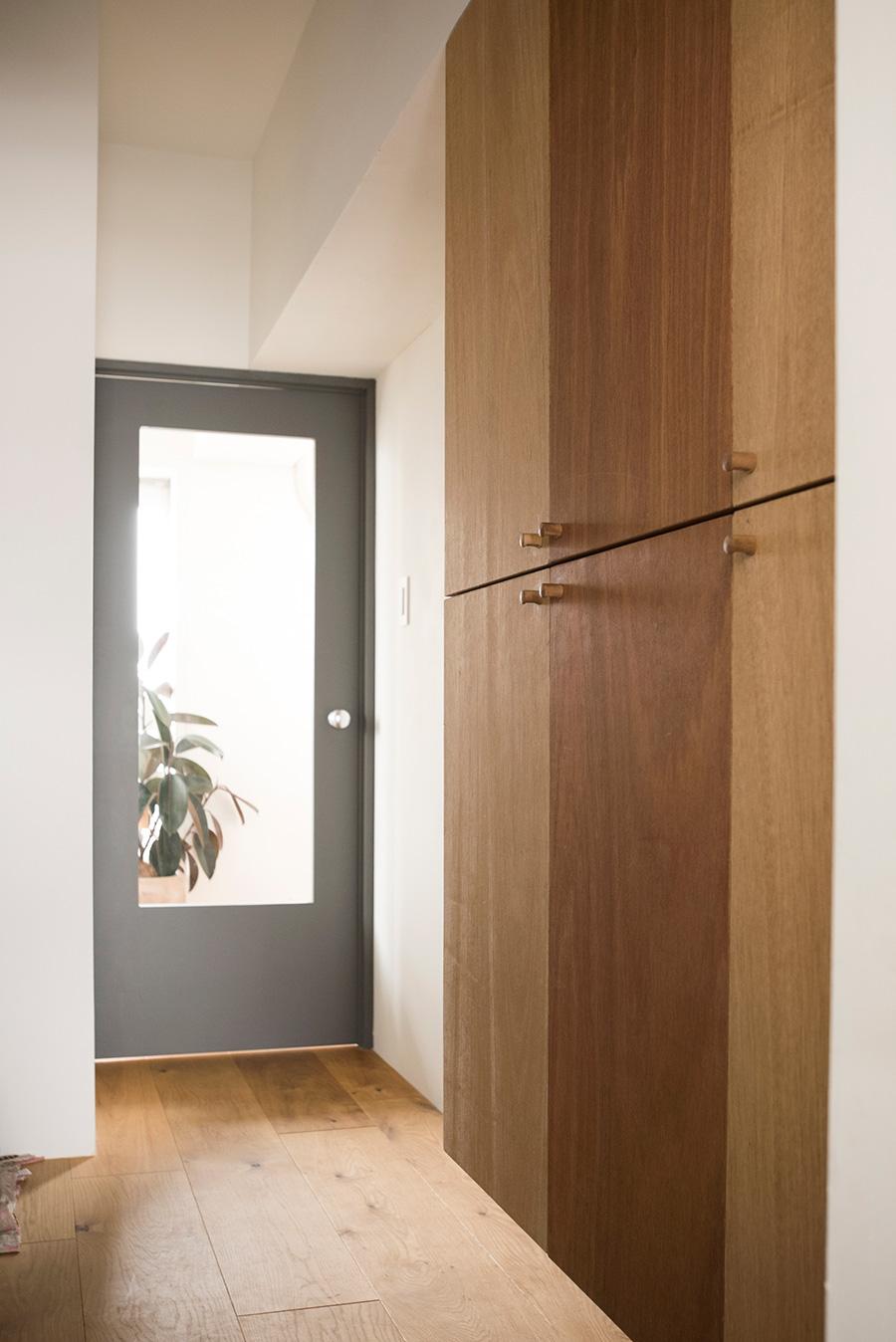 暗くなりがちな玄関に続く廊下には、ガラスを入れたドアを選んで光の通り道を確保。靴箱もラワンで造作。不揃いな木の色を逆に活かしたデザインに。