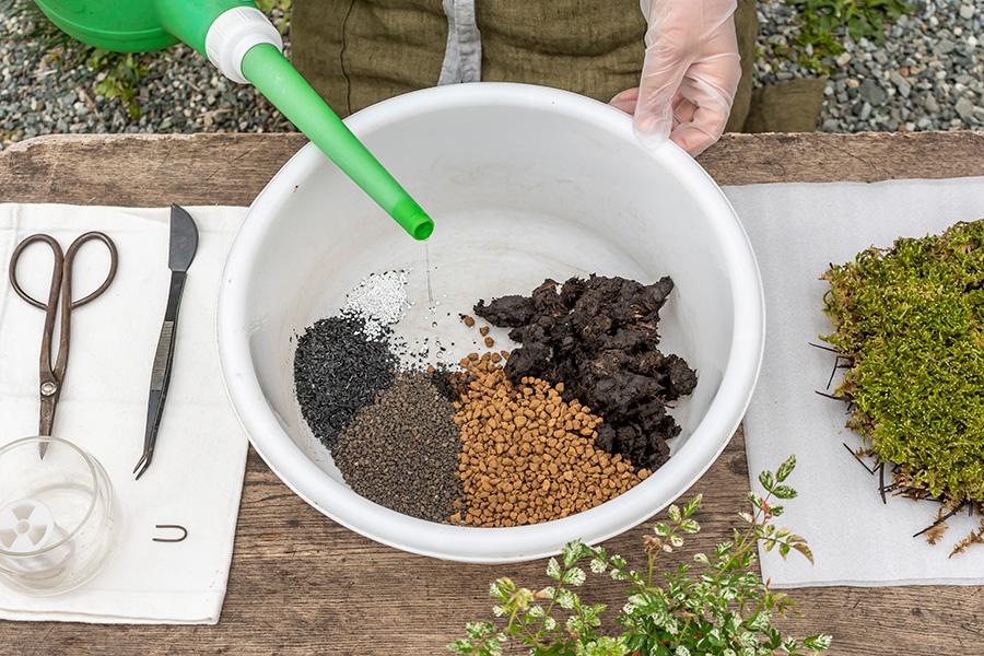 ①土を入れたバケツに、少しずつ、土に染み込む程度に水を注ぎ入れる。