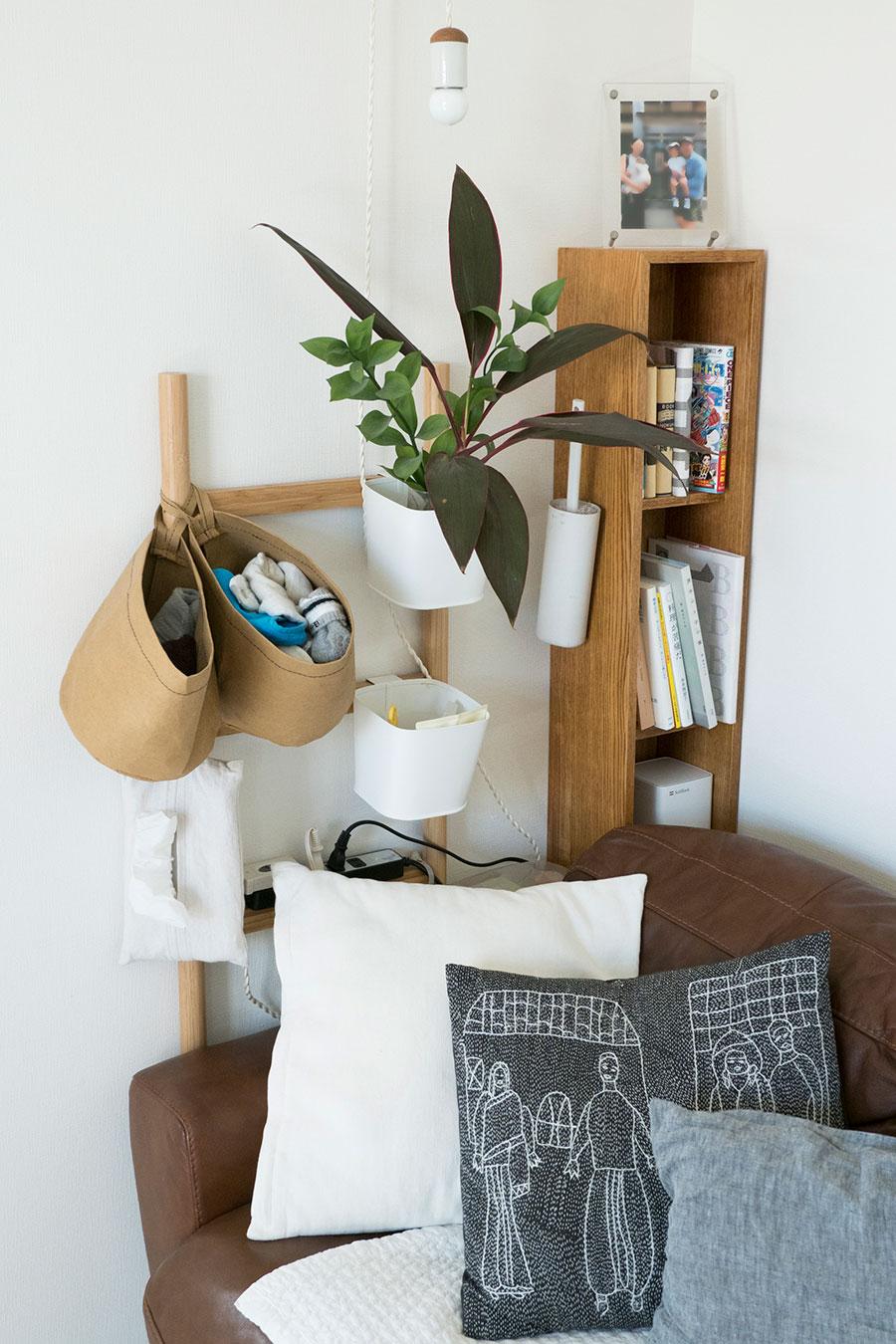 家具を置くかわりに、はしごにバッグやボックスをぶら下げることで収納に。子どもの下着類やティッシュ、掃除道具などリビングで使いたいものをまとめている。はしご上に置いたタップは抜き差しがしやすく、掃除もラク。