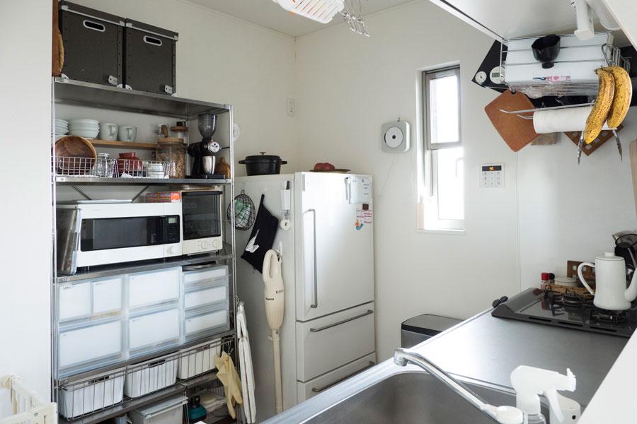 シンクの反対側にはシェルフを置いて収納兼、家電置き場として。冷蔵庫はコンパクト化したことで、逆にストックを控え食材のロスがなくなったそう。フィルター式の掃除機は、大きいゴミ箱の近くがゴミ捨てに便利なので、キッチンをホームポジションに。