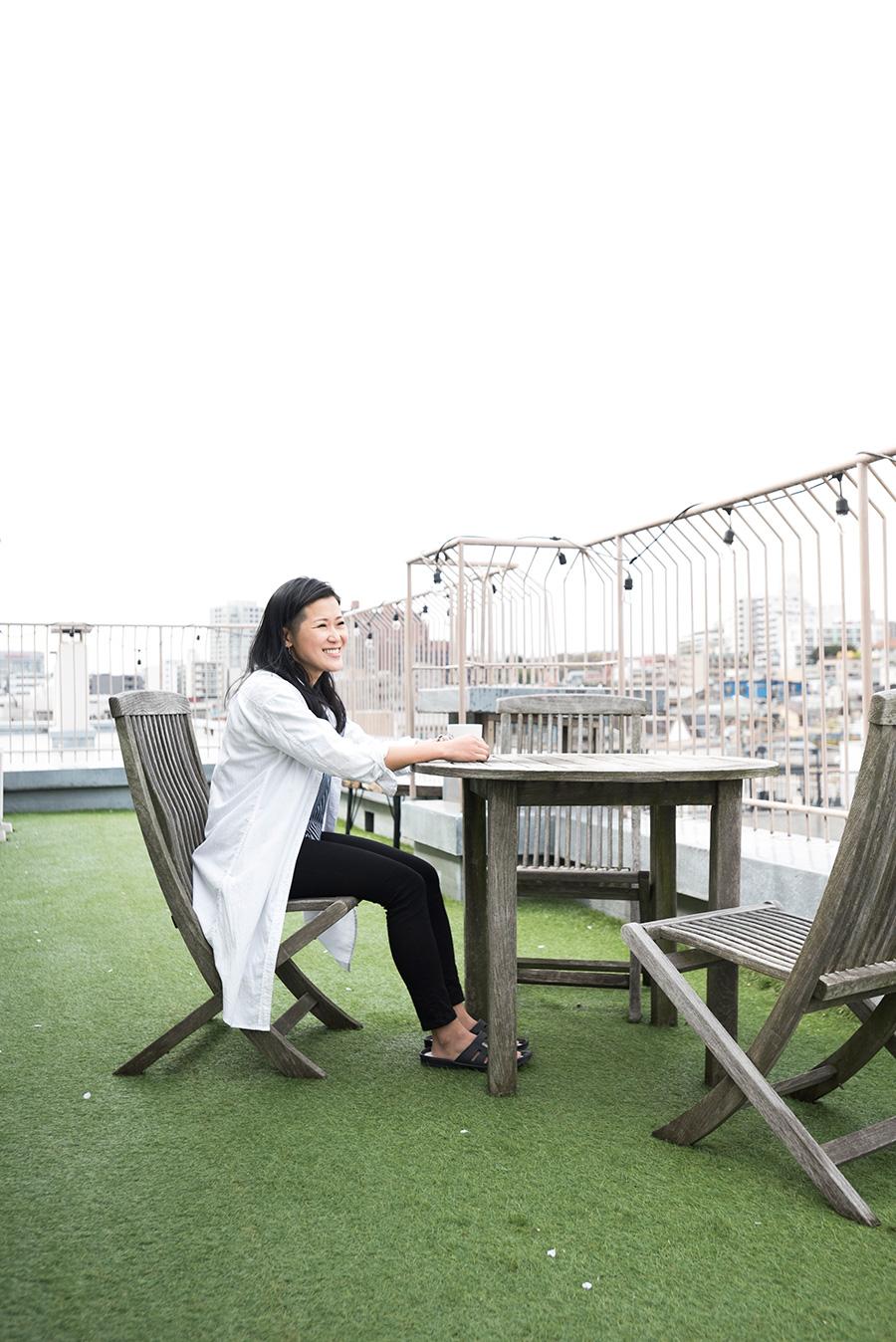 「仕事の合間にバルコニーで寛ぐ時間が好き」というグラフィックデザイナーのカトウアヤコさん。大好きなものづくりを活かした生活を楽しむ。