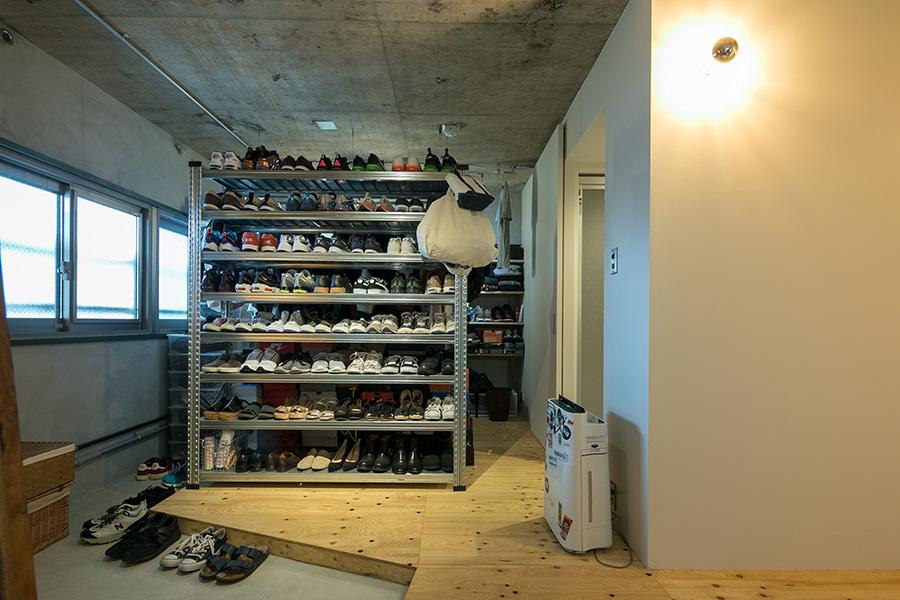 靴のコレクションは壮観。「メタルシステムのラックは、靴がピッタリ入るように棚板の高さを調整しました。玄関の土間は靴がたくさん置けるように、奥まで伸ばしてもらいました。ここに自転車を置くこともできます」