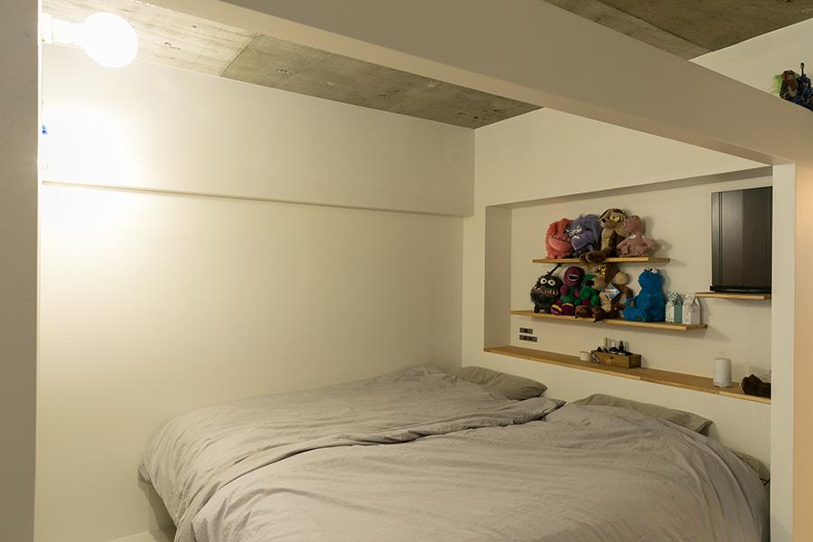ベッドルームは扉をつけず、リビングの一角に。間仕切り壁と天井の間を開けたパーテーションのような造りになっている。「風通しがよく、心地いいです」