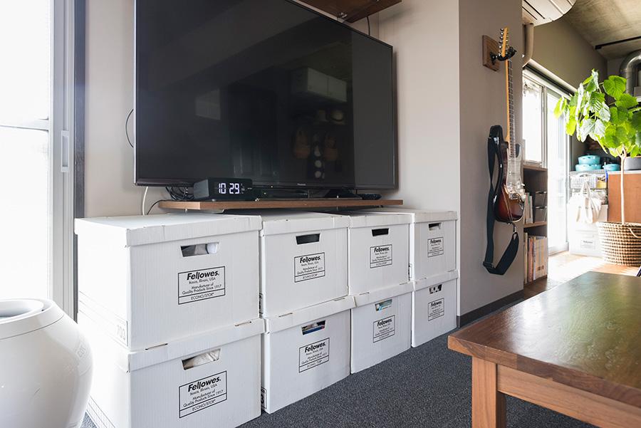 棚柱を使って渡した棚板をTVボードに。その下にバンカーズボックスを置いて、収納をたっぷり確保。限られたスペースを有効的に使うアイデア。