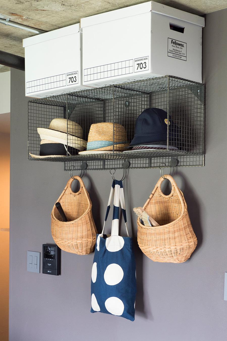 ザ・コンランショップのワイヤーシェルフを使って「見せる収納」に。お出かけ時の帽子はいつもここから。お掃除グッズを入れているカゴは、花器として販売されていたものだそう。