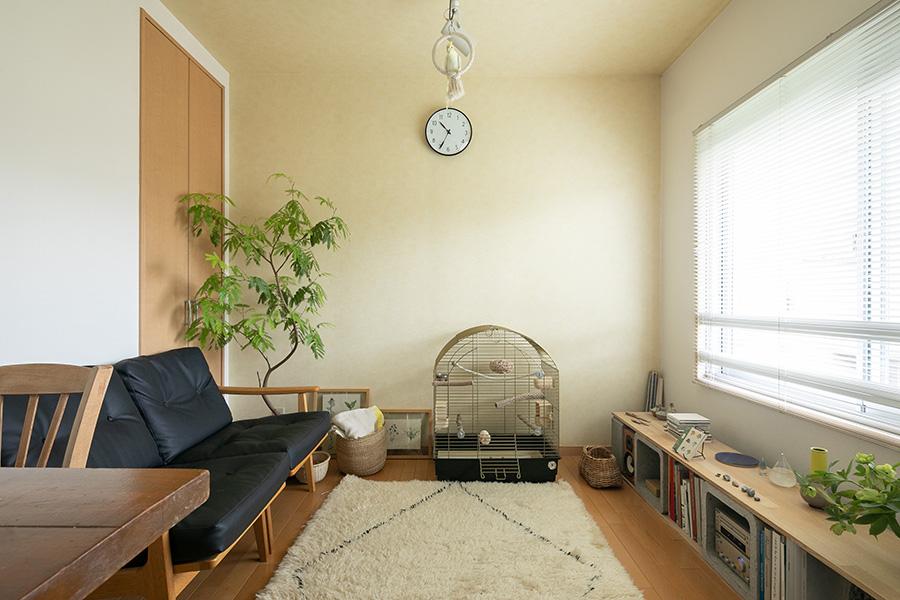 リビングスペースは正面と天井が淡いクリーム色の壁紙。張り地を替えながら長年使っているマルニのソファとベニワレンのラグ。
