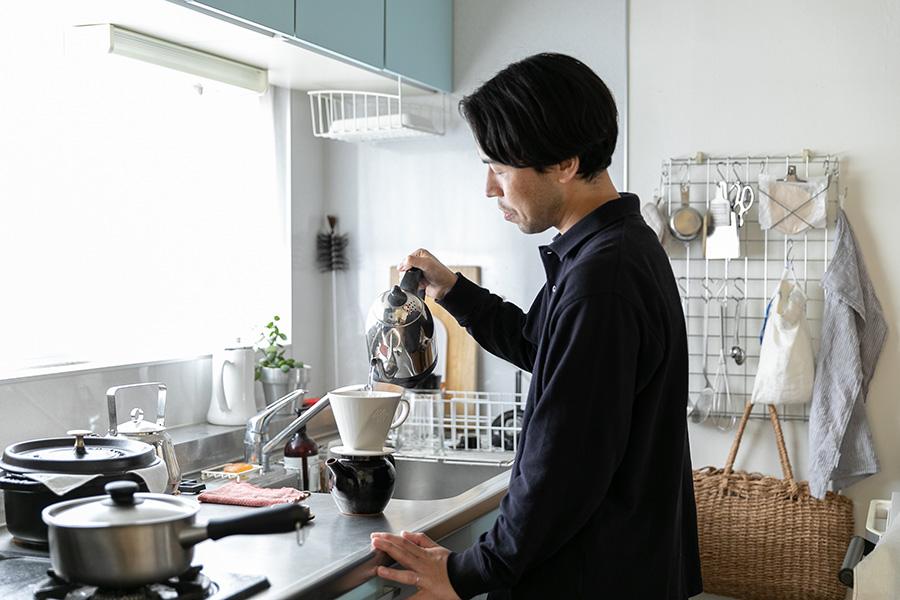 明るいキッチンでコーヒーを淹れるご主人。