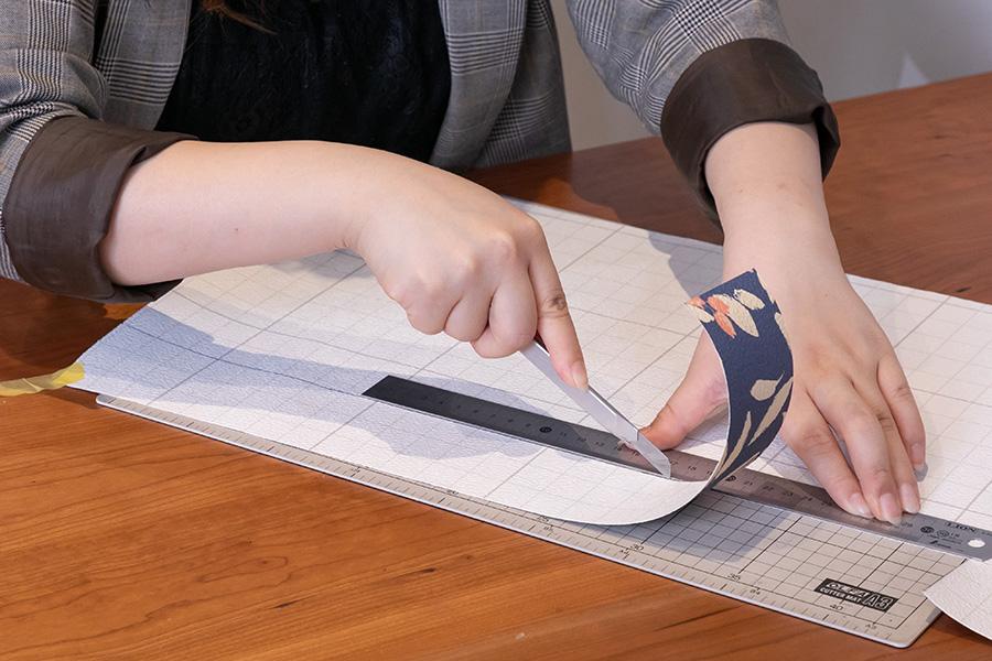 カッターを定規に当てながらカット。壁紙の裏紙は1cmごとの方眼になっていて、まっすぐのカットがしやすい。