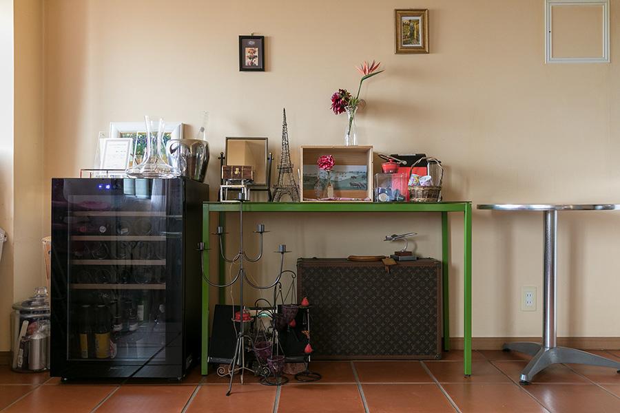 差し色の緑が効いた棚やさりげなく飾られたアートが、こなれ感を醸し出す一角。左にあるのはワインセラー。