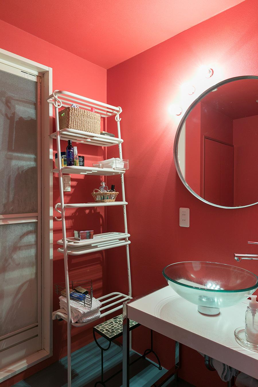 洗面所は、赤を効かせてアーティスティックな雰囲気に。「丸い鏡と三つ並べたランプもお気に入りです」と藤山さん。