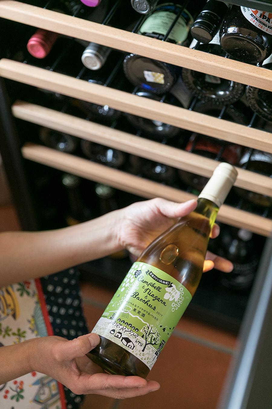 ワインセラーには常にお気に入りのワインをストック。教室では2,000円前後のワインを紹介することが多いという。手にしているのは、富良野の多田農園ワイナリーの白。