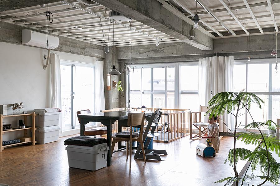 4方からたっぷり日差しが入る明るい住まい。リノベの際に残した天井の野縁の枠組みを自分たちで白に塗装。床はDIYでOSMOカラーで仕上げたラーチ合板。「将来的にこの上からフローリングを張るかもしれません」