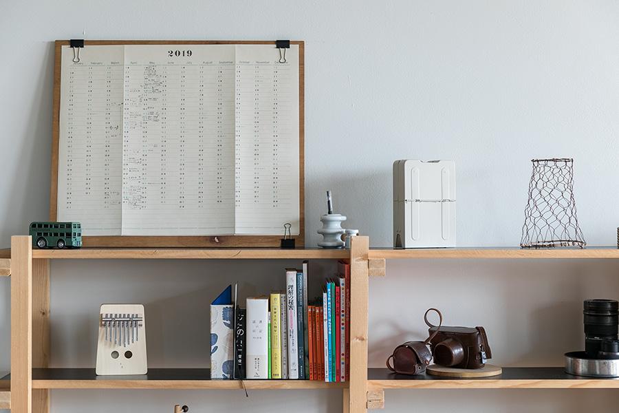 黒の天板の棚は、以前使っていたテーブルの木材を流用してDIYしたもの。空間を生かしながらセンスよく好きなものを並べて。