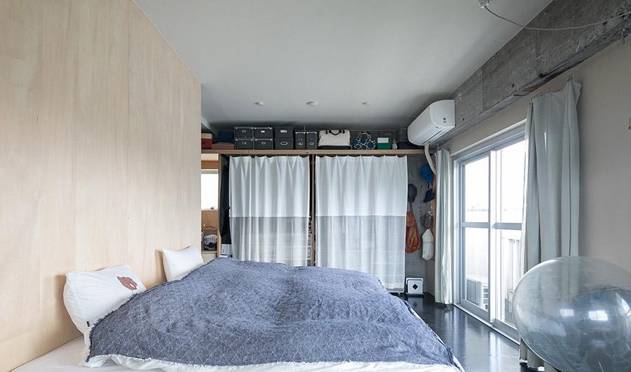 ベッドルームの物入れのカーテンは、前の家で使っていたものの下に半透明の素材の布を継いだハンドメイド。美しいデザインのカーテンにリメイクされた。