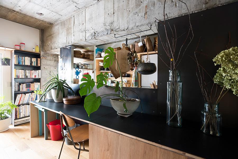 キッチン背面のカウンターには黒皮鉄をあしらった。生の素材感が自然な表情を出し、コンクリートの雰囲気と調和する。奥の本棚も黒皮鉄で作ったもの。「べったりとした黒にならないのが魅力です」。