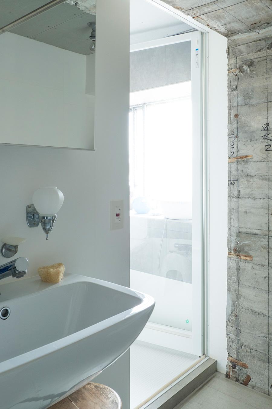 奥はハーフユニットにした窓のあるバスルーム。サンワカンパニーで選んだ洗面はクラシカルな雰囲気。