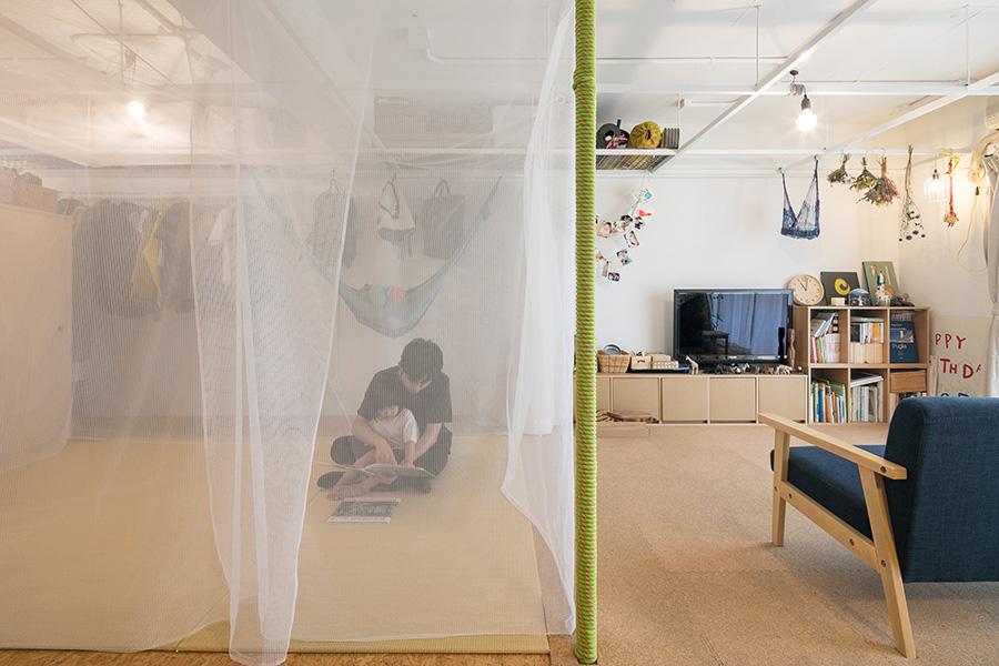 夏用の蚊帳を下ろした様子。1枚の布が空間をゆるやかに分ける。実際には寝るときにだけ蚊帳を下ろしているそうだ。