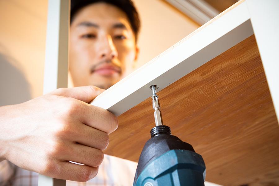 スチールの棚受けにはあらかじめ穴が開いているので、そこに木ネジを使って固定していく。