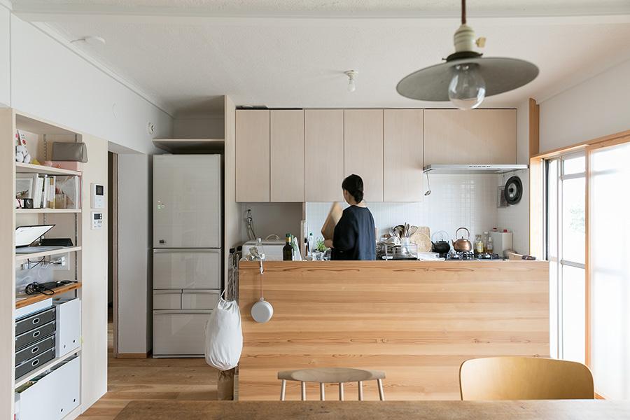 冷蔵庫の右側に洗濯機が。キッチンのアイランドタイプのカウンターが、作業場と収納に役立っている。