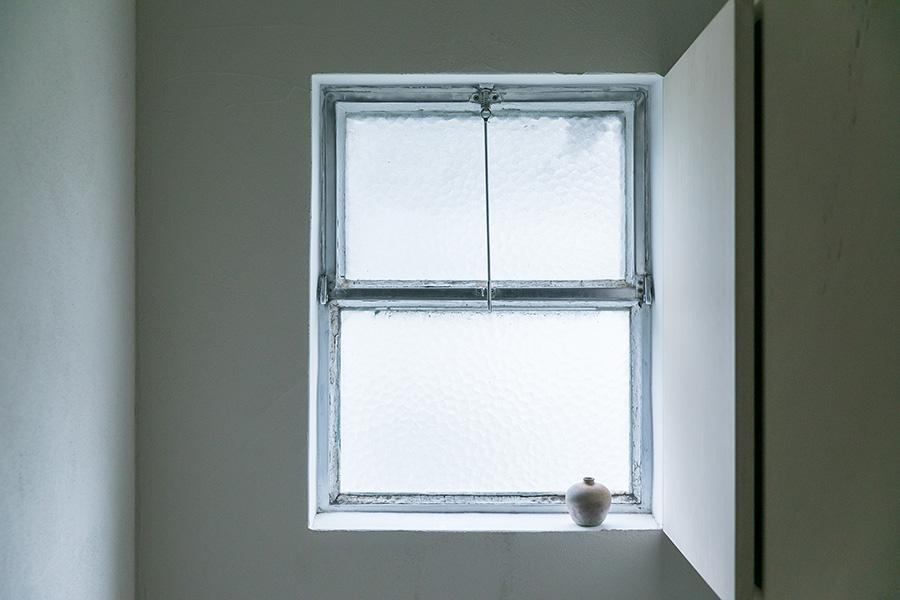 古いまま残してある洗面所の窓枠。右側は収納棚が付いているが扉を開けると裏側にミラーが貼ってあり使い勝手が良い。