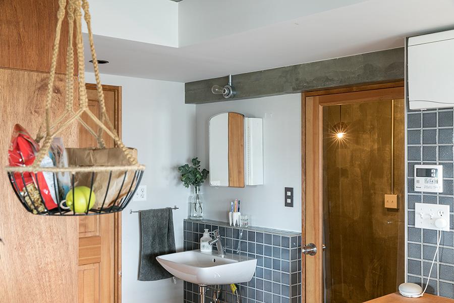 オープンな洗面スペースにもグレーのタイルを貼って、キッチンとつながりを持たせた。