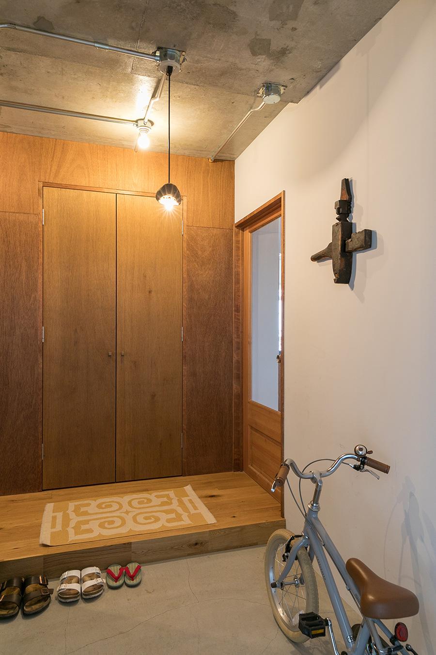 モルタルの玄関。物入れはラワン材。壁にはアフリカのドゴン族の家の鍵を飾った。
