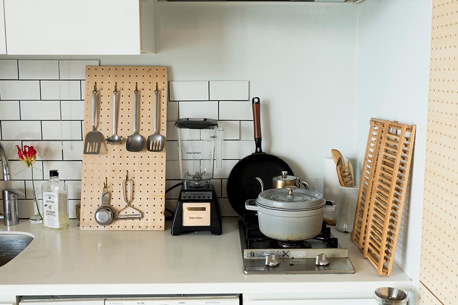 有効ボードに調理器具を吊るして収納。2口のガスコンロでは、ストウブ×スノーピークのコラボ鋳物鍋が活躍している。サブウェイタイルは施工途中…。