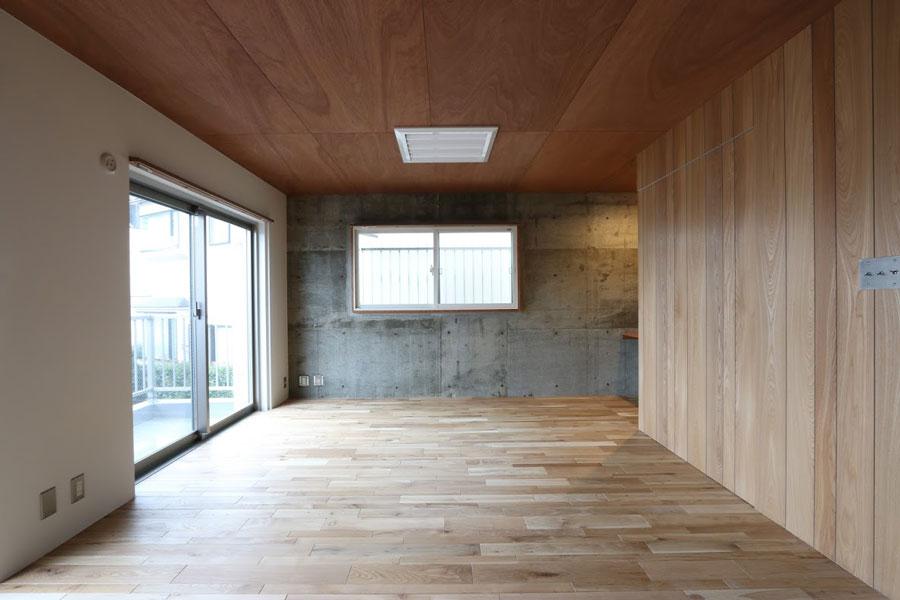 天井をラワン材、床はソリッドオークフローリング、アクセントウォールはウッドウォールパネルを選択。正面はコンクリート現し、左の壁は白に塗装した例。