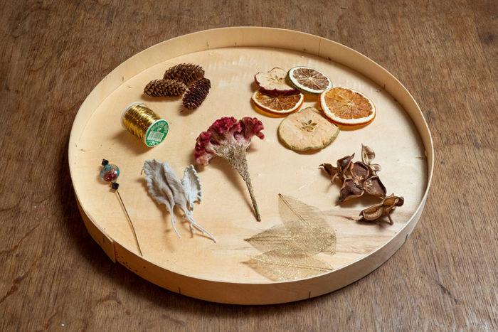 リンゴやオレンジなどのドライフルーツ、綿の実の殻、ゴールド加工した葉脈、松かさ、ケイトウ、シロタエギクを、ゴールドのワイヤーでつないでいく。後は穴を開ける針があればOK。