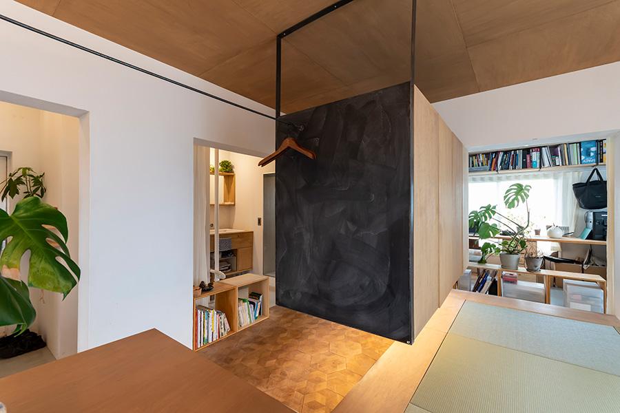 和室、ワークスペース、洗面を、浮き上がった黒い箱(収納)がゆるく仕切る。和室には縁甲板を用いた。