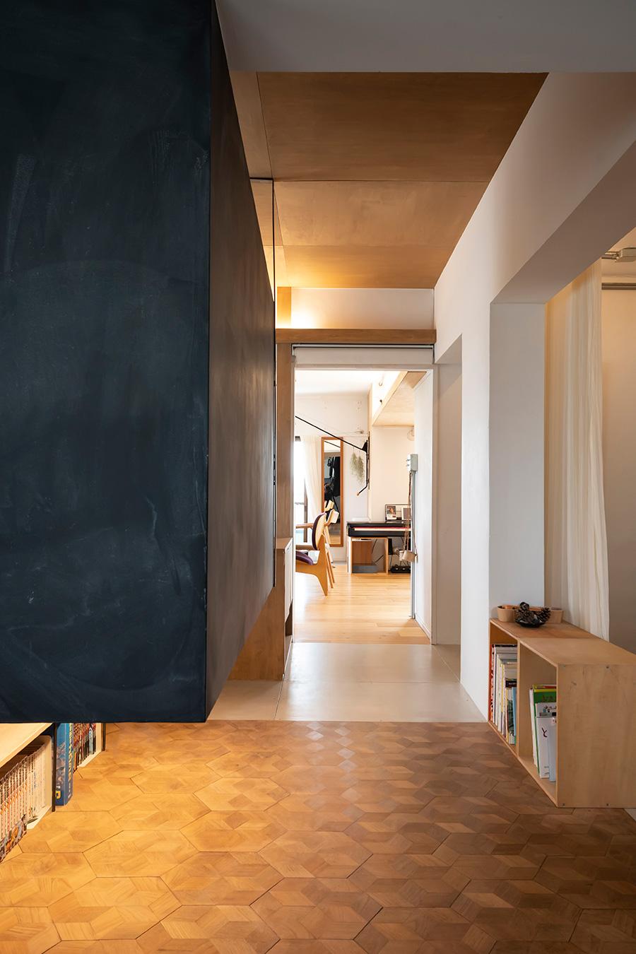 廊下の床は素材で切替えて、空間をさり気なく分けている。六角形のパーケットフローリングは日本の伝統的な亀甲模様。和をモチーフにするため、細かなところにも取り入れた。