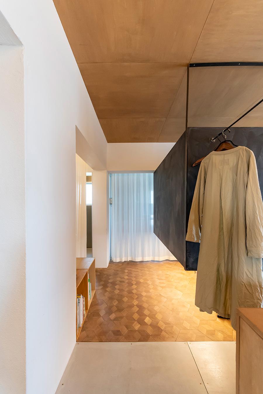 手前の床は玄関からつながっているフレキシブルボード。アイアンで造作したバーはコートハンガーに。ガーゼのカーテンを引けば、ゆるやかに空間を仕切ることができる。