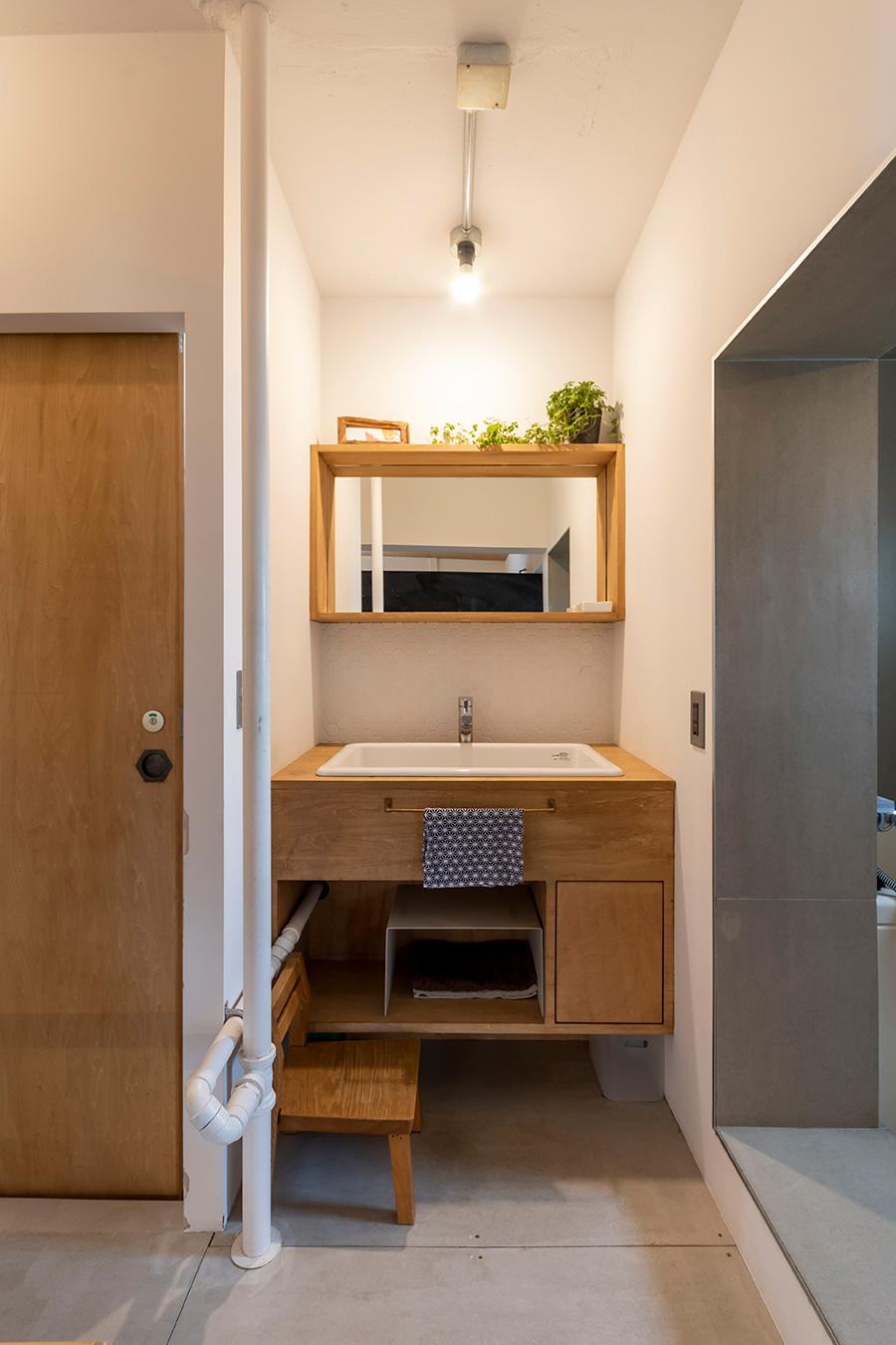洗濯機をキッチンに移動しすっきりさせた洗面は、玄関からもアクセスできて動線がいい。。右手の扉のないバスルームは、湿気が籠らないメリットも。トイレの引き戸の取っ手も亀甲模様に。
