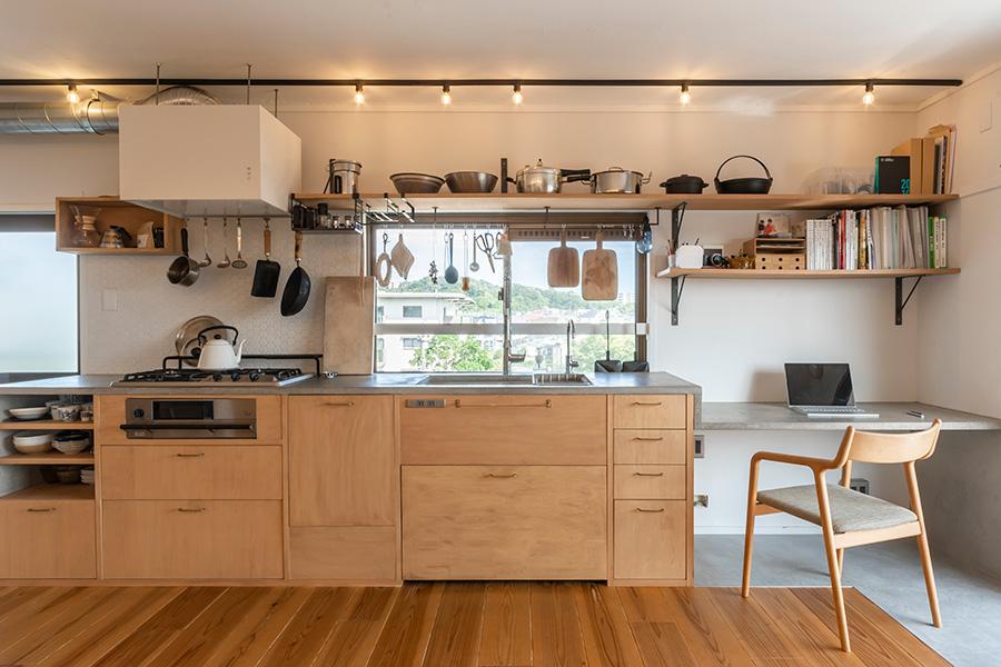 作業をしながら外の景色が楽しめる気持ちのいいキッチン。ベランダに面した縁側のモルタルは、冬は蓄熱、夏はひんやりとして効率的だそう。