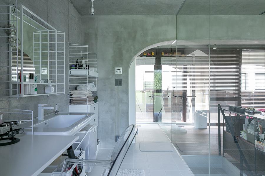 リビングルームとガラス一枚で隔てられた広々とした洗面スペース。奥がバスルーム。