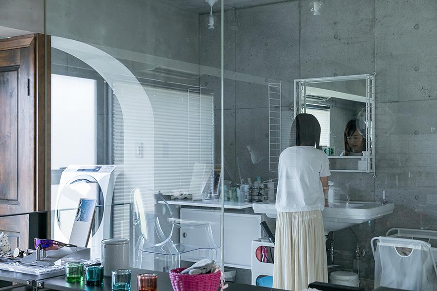 リビングと天井までのガラスで隔てられた洗面所スペース。白で統一されたスペーシーな空間への入り口は、左側の重厚な木の扉。