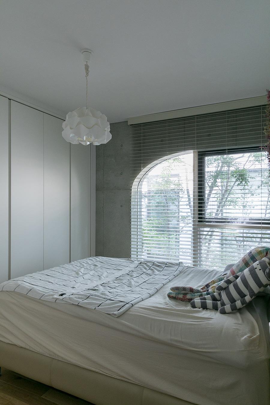 コーポラティブハウス共通の意匠である曲線の窓が優美な曲線を描くベッドルーム。