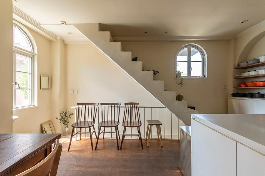"""昔の階段や窓をそのまま残し、壁を漆喰塗装に。微妙な白のトーンが光を受けて陰影を生み出す。床は""""バーガンディー(ブルゴーニュ)オーク""""という名の無垢のオーク材。"""