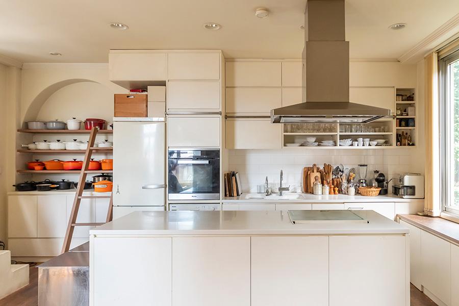 LDKのキッチン側は白をベースにした空間に。アイランドはダイニング側にも収納を設けた。吊り戸棚の上段のものを取り出すときは、ハシゴを移動させる。