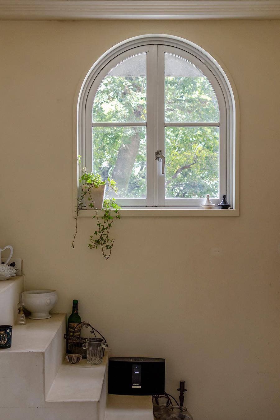 アーチ型の窓がアプローチの緑を切り取る。階段はディスプレイスペースに。
