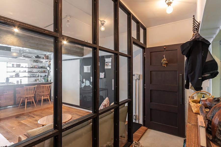玄関土間から室内を見る。壁ではなくガラスの格子窓で仕切られているので、広さを感じられる。