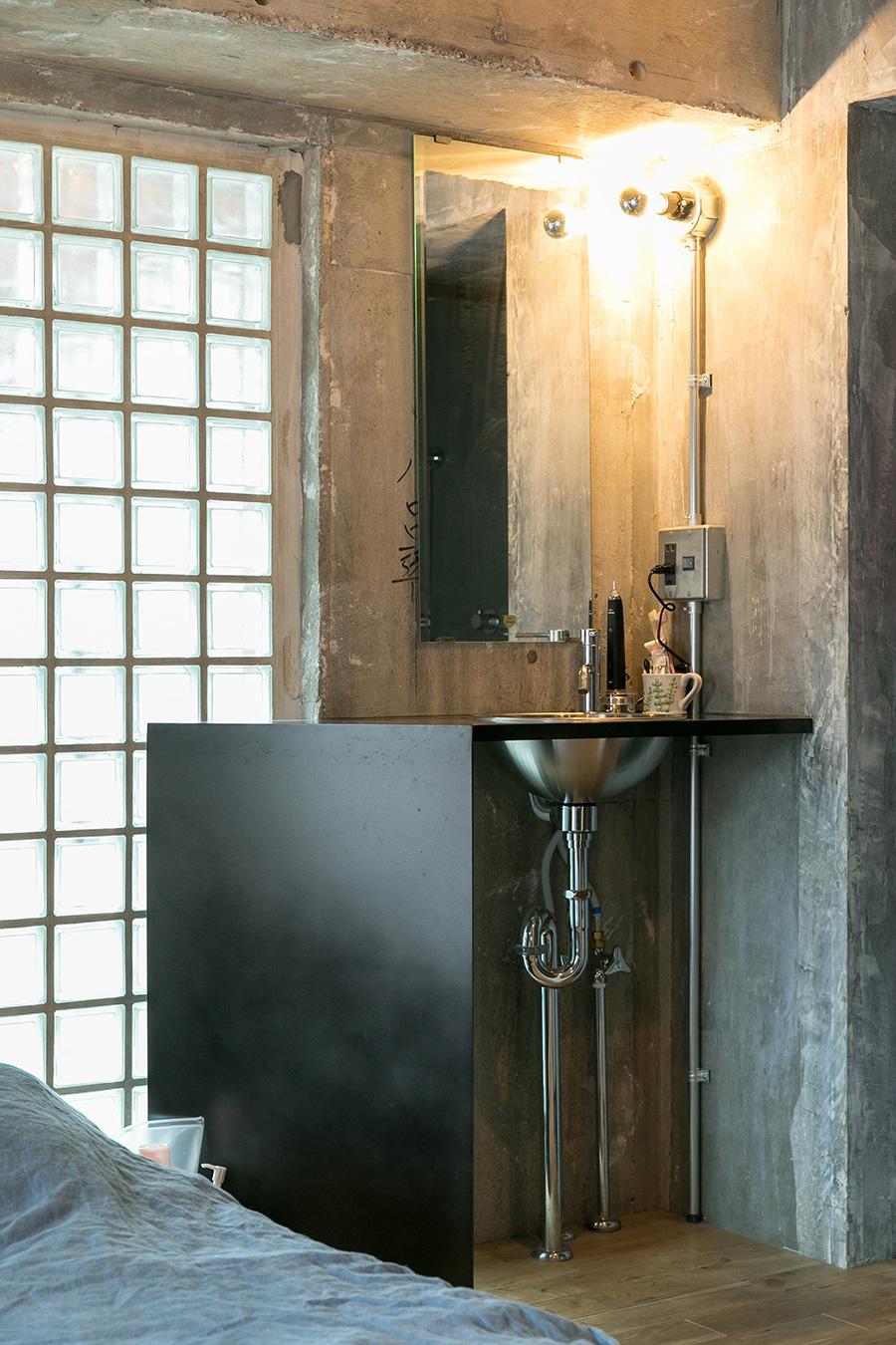 洗面台はアイアン素材で作ったオリジナル。ガラスブロックを見せながら、斜めに空間を切り取っている。