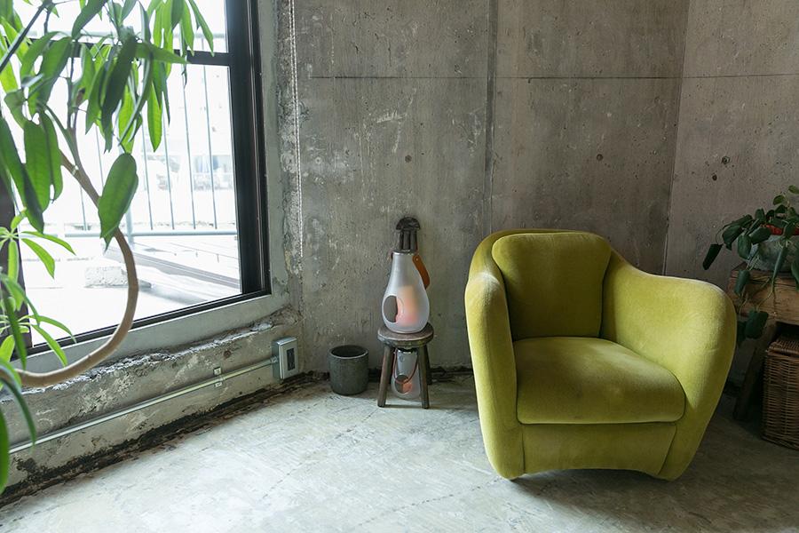 一人サイズのグリーンのソファはIDÉEで。コンクリート現しの空間によく似合う。