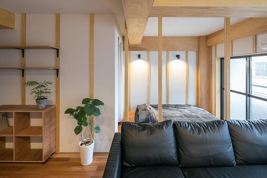 奥に見えるのが寝室スペース。扉は付けず、床を一段上げて3本の独立柱をつけることで、ゆるやかに区切った。白い壁と木のぬくもりに、シックな黒い家具や小物を同居させるのが、インテリアのポイント。